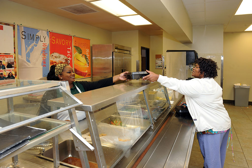 A nurse is picking up her dinner in the BayPointe cafeteria.
