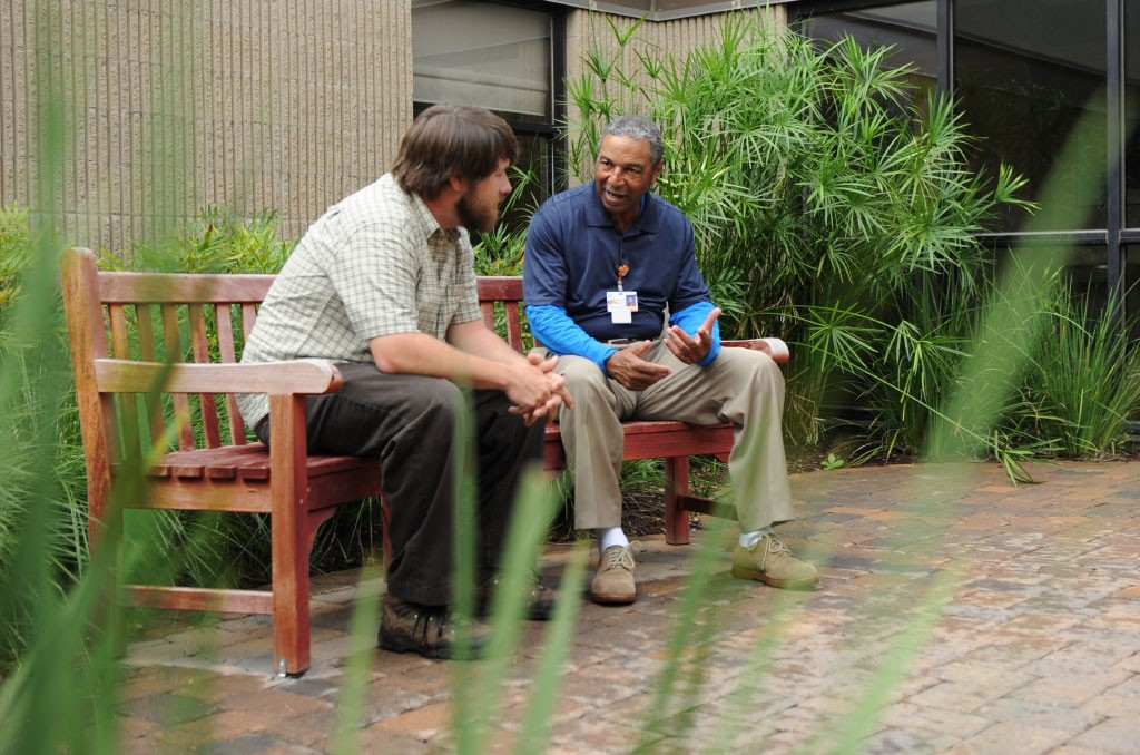 An adult male patient consults with a therapist in the peaceful courtyard setting at EastPointe