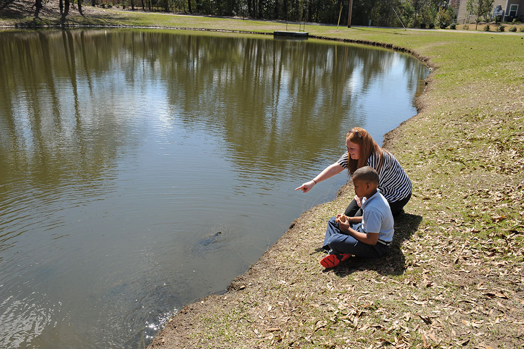 A young male patient and a therapist observe the turtles while visiting the lake at BayPointe Hospital