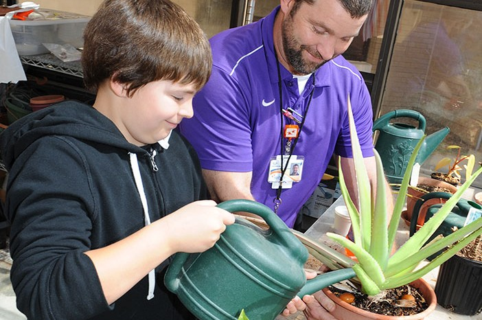 A counselor works with a young male patient teaching him how to tend to plants.